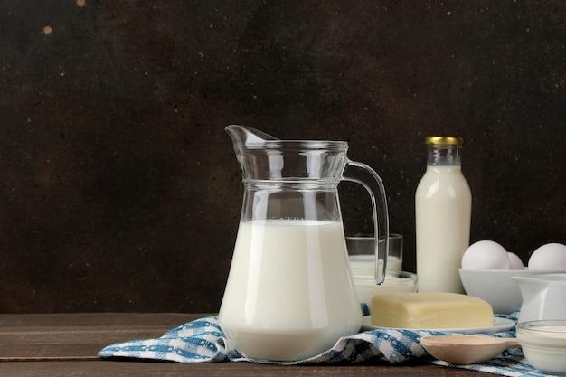 Milchprodukte. milch, sauerrahm, käse, butter und hüttenkäse auf einem braunen holztisch. platz für text