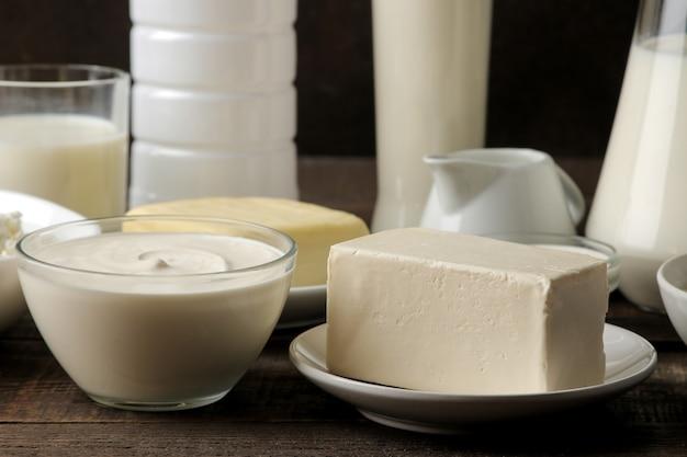Milchprodukte. milch, sauerrahm, käse, butter und hüttenkäse auf einem braunen holztisch