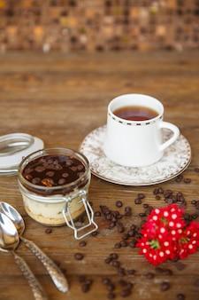 Milchpudding mit schokoladenstückchen und soße, serviert mit tee
