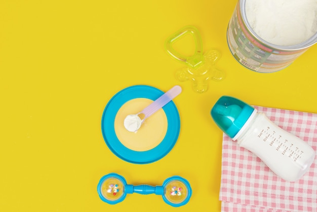 Milchpulver für baby im messlöffel in dose und milchflasche auf stoff auf gelb