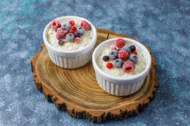 Milchreis mit gefrorenen blaubeeren und himbeeren in weißer schüssel