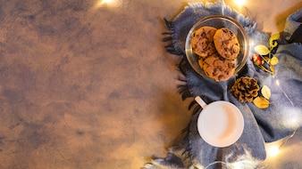 Milchschale mit Keksen auf blauem Plaid