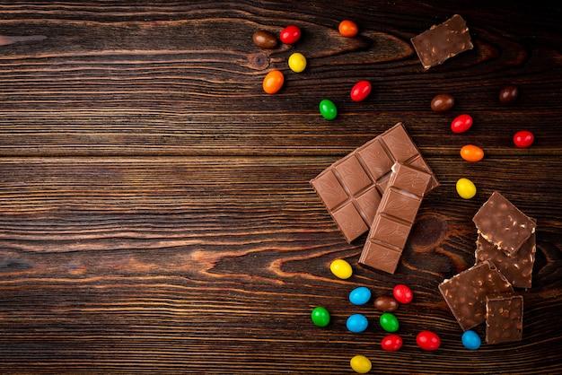 Milchschokolade und farbe dragee auf dunklem holztisch.