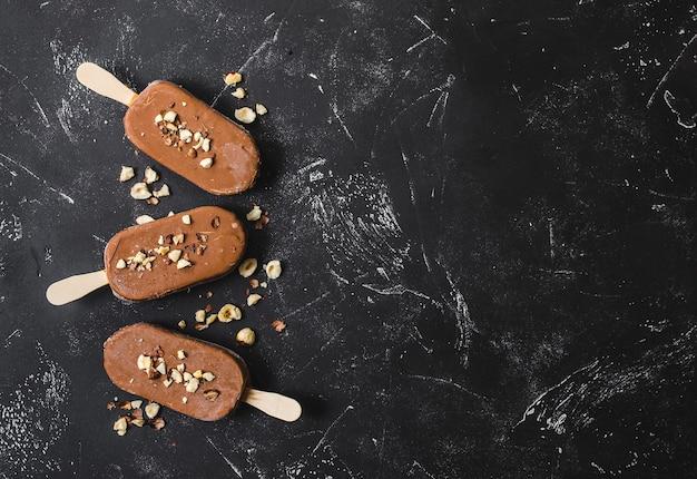 Milchschokoladen-eis am stiel mit haselnüssen. eiscreme-eis am stiel bedeckt mit schokolade, stöcken, schwarzem steinmarmorhintergrund.