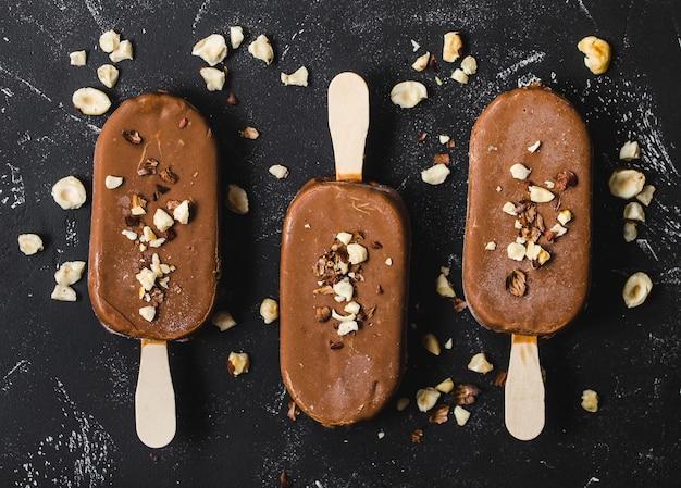 Milchschokoladen-eis am stiel mit haselnüssen. nahansicht. eiscreme-eis am stiel bedeckt mit schokolade, stöcken, schwarzem steinhintergrund.