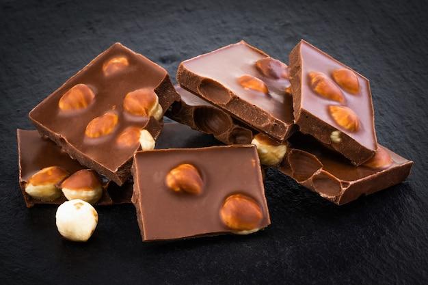 Milchschokoladenstücke mit nüssen auf dunklem hintergrund.