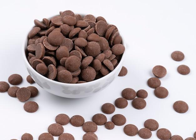 Milchschokoladentropfen in weißer schüssel, zutat für kekse und muffins.