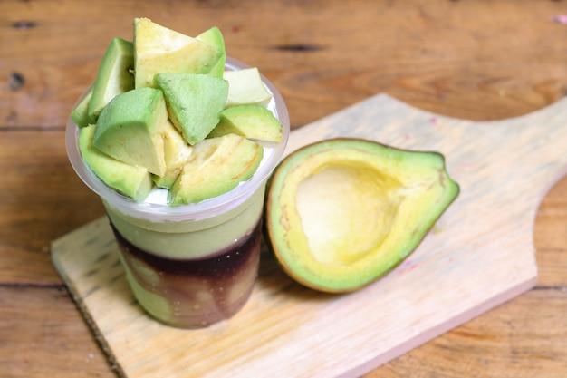 Milchshake mit avocadostücken, in plastikbecher, lecker und frisch