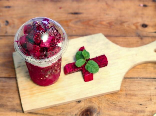 Milchshake mit drachenfruchtstücken, in plastikbecher, lecker und frisch