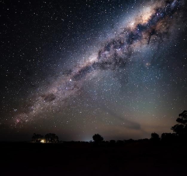 Milchstraße über silhouette eines bauernhauses. astro-fotografie-konzept. raumkonzept