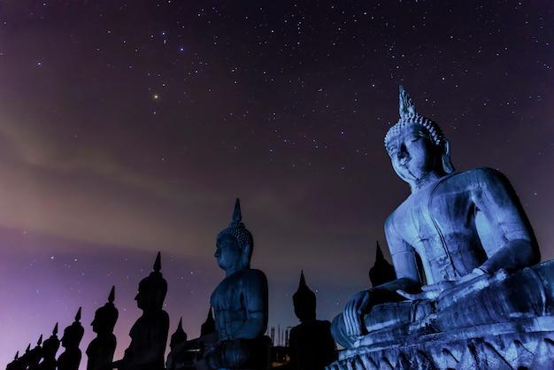 Milchstraßegalaxie mit dunkler filterart buddha-statur