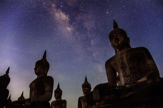 Milchstraßengalaxie mit dunkler filterart der buddha-statur