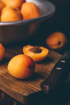 Milde aprikosen mit messer über altem holzschneidebrett und metallschale mit früchten