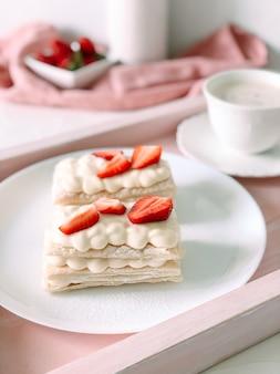 Milfey kuchen mit sahne und erdbeeren und tasse kaffee cup