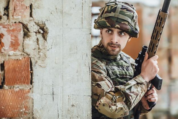 Militär in form hält in den händen eines großen gewehrs, sieht aus wie gegner aus der ecke