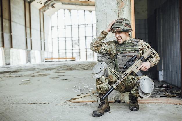 Militär in form hält in den händen eines großen gewehrs
