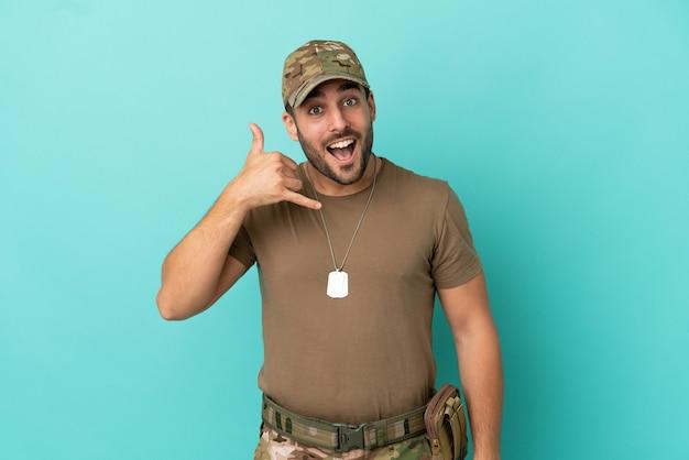 Militär mit hundemarke über isoliert auf blauem hintergrund, der telefongeste macht. ruf mich zurück zeichen