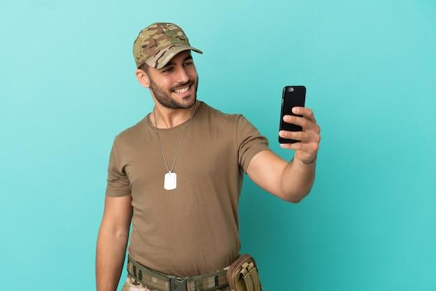 Militär mit hundemarke über isoliert auf blauem hintergrund macht ein selfie