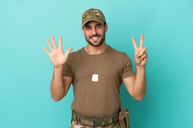 Militär mit hundemarke über isoliert auf blauem hintergrund und zählt sieben mit den fingern