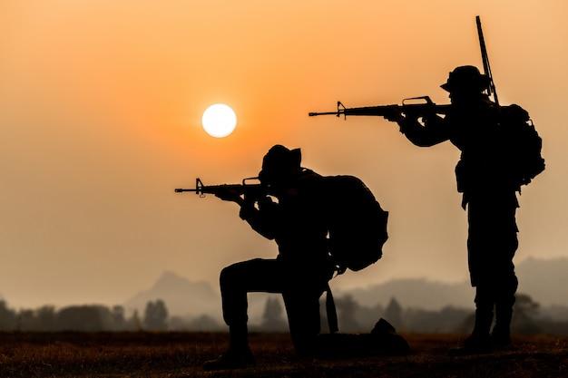 Militär- oder soldatschattenbilder auf sonnenuntergangshimmelhintergrund, voll ausgestatteter und bewaffneter soldat, der auf schattenbildumgebung im sonnenuntergang steht.
