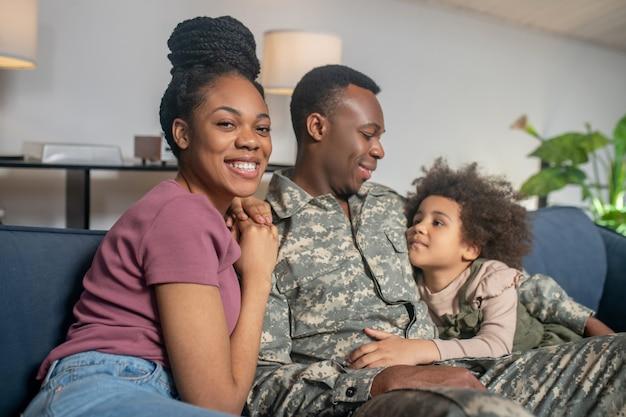 Militär, papa. soldat junger dunkelhäutiger mann in uniform sitzt mit glücklicher frau und kleiner tochter, die sich im urlaub zu hause auf dem sofa umarmen