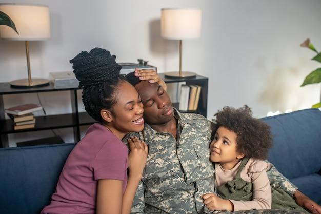 Militär, urlaub. militärischer junger erwachsener dunkelhäutiger mann mit frau und kleiner tochter, die glücklich auf dem sofa in einem gemütlichen zimmer zu hause sitzen