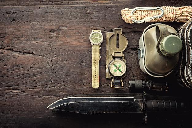 Militärische taktische ausrüstung für den abflug. zusammenstellung des überlebens ausrüstung auf hölzernem hintergrund wandernd