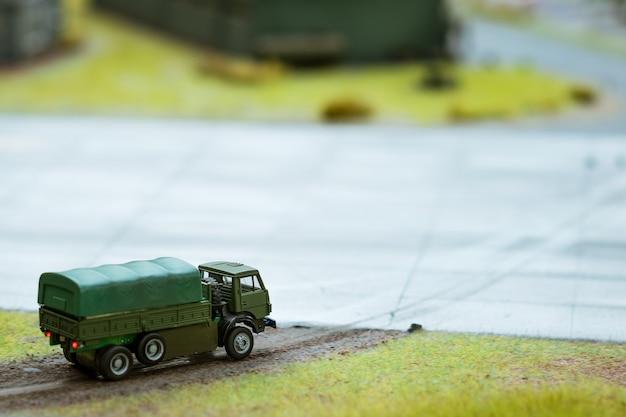 Militärlastwagen in miniatur, auf die straße gehend. weicher fokus