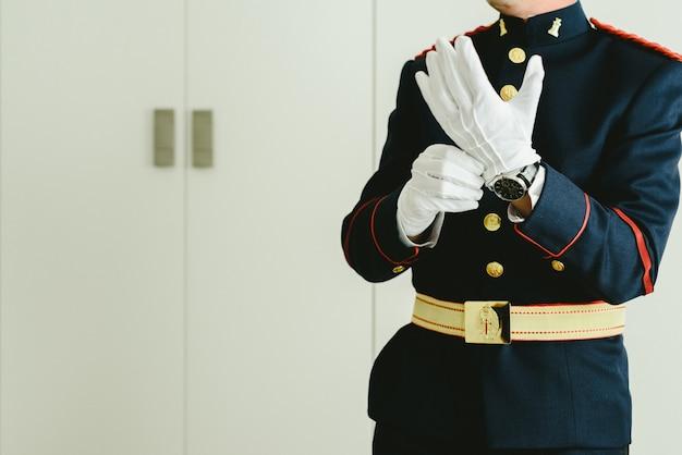 Militärmannhände, die auf einige elegante weiße handschuhe sich setzen.