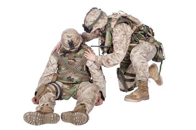 Militärmediziner, kommando, das für die schultern zittert, versucht, das bewusstsein zu wecken, den zustand des bewusstlosen, verwundeten soldaten oder kameraden zu überprüfen, einzeln auf weiß. rettung von verletzten, sterbenden infanteristen