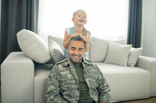 Militäroffizier lächelt. militäroffizier lächelt, während er endlich zeit mit seiner süßen tochter verbringt