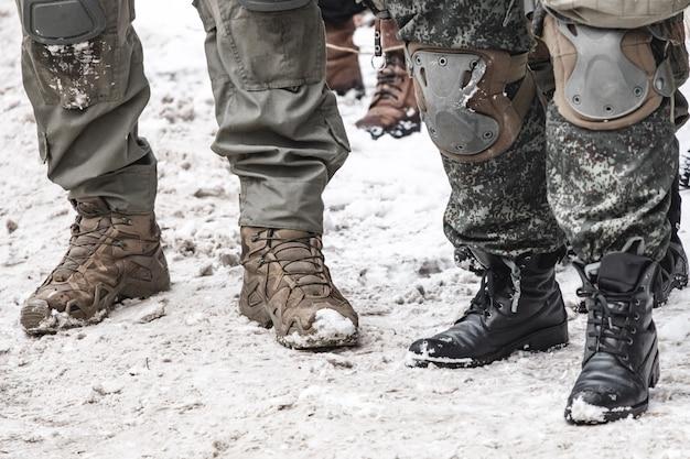 Militärs in spezialuniform und stiefel standen im winter draußen.