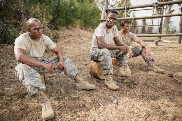 Militärsoldaten, die sich während des hindernistrainings im bootcamp entspannen