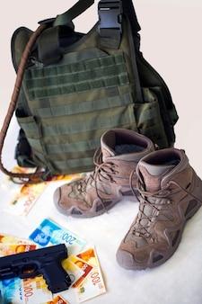 Militäruniform und ausrüstung. körperpanzerung, schwarze waffe und stiefel mit banknoten der israelischen new shekels-draufsicht. haufen israelische geldscheine und pistole auf weißem hintergrund. visuelles konzept für soldaten
