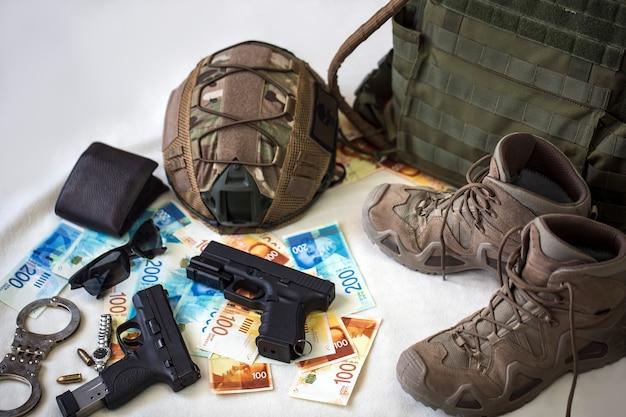 Militäruniform und ausrüstung, munition. körperpanzer, waffen, kugelsicherer helm, handschellen, sonnenbrillen und militärstiefel mit banknoten der israelischen neuen schekel. waffen für airsoft- und urbane proteste