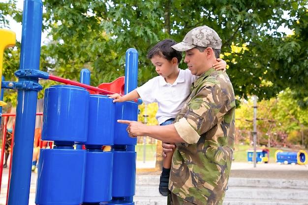 Militärvater, der mit kleinem sohn im park geht, jungen in den armen hält und spielgeräte studiert. seitenansicht. elternschafts- oder kindheitskonzept