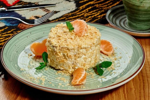 Mille-feuille-kuchen napoleon nach russischer art mit zarter buttergebäck-creme überzogen mit krümeln, garniert mit mandarinenspalten und frischer minze