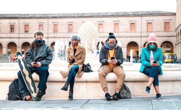 Millenial freunde sehen video auf smartphones mit gesichtsmaske auf covid zweite welle