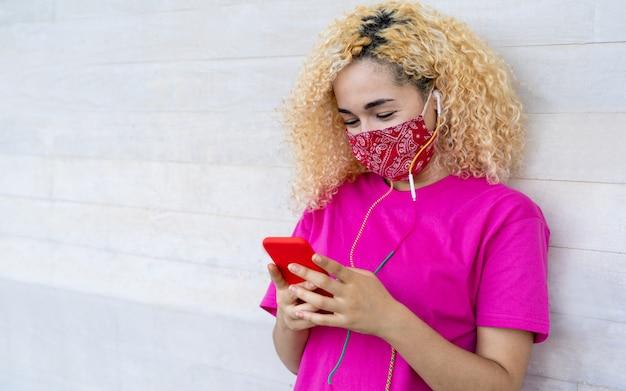 Milleniales mädchen, das handy beim tragen der gesichtsmaske während des ausbruchs des coronavirus verwendet