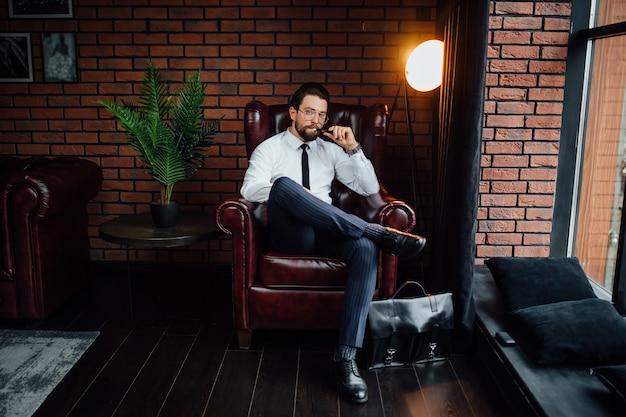 Millionärsmann, der sich ausruht und entspannt, während er auf dem sofa im luxuszimmer sitzt. gut aussehender mann, der zigarre oder iqos raucht.