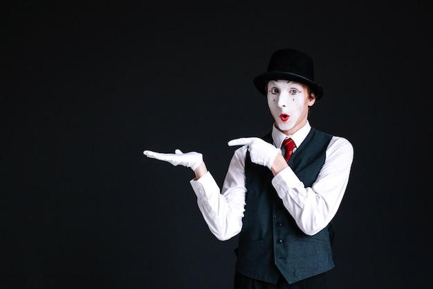 Mime zeigt auf etwas unsichtbares auf seiner handfläche