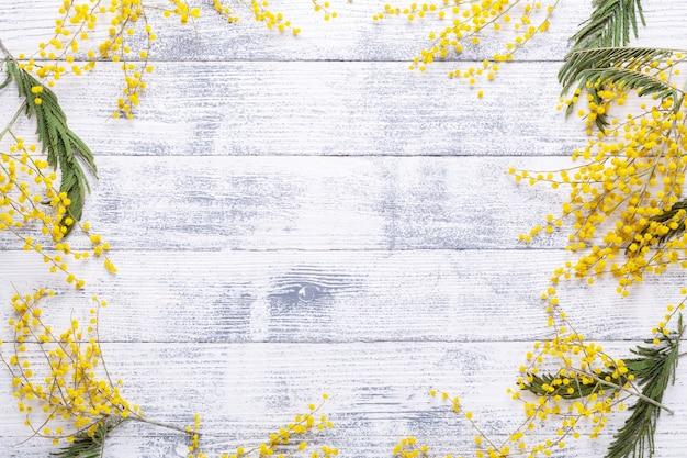 Mimosenblumen auf einem holztischhintergrund