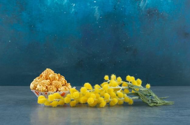 Mimosenpflanze durch einen kleinen haufen popcorn mit karamellgeschmack auf blauem hintergrund. foto in hoher qualität