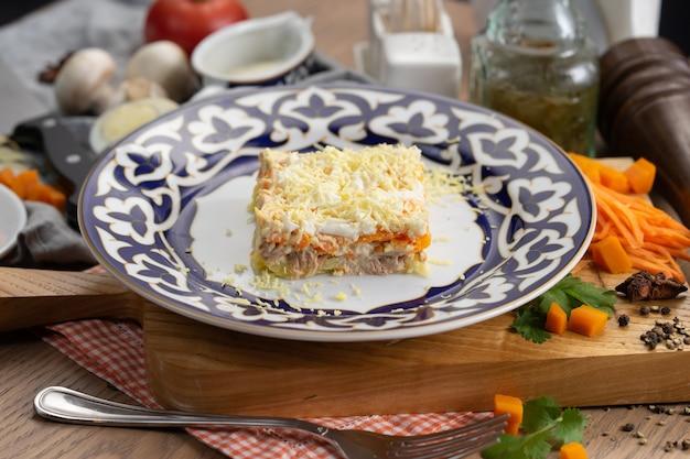 Mimosensalat in einem teller mit einem traditionellen usbeken
