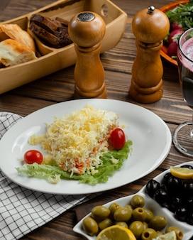 Mimosensalat mit karotten, eiern, kartoffeln und käse