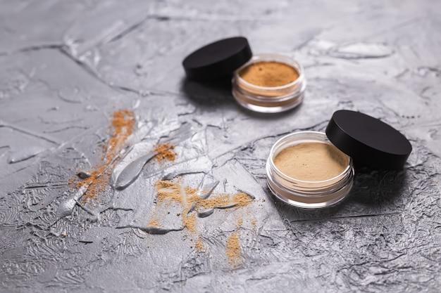 Mineralpulver in verschiedenen farben mit pinsel für make-up auf holzuntergrund