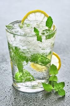 Mineralwasser mit zitrone und minze im glas auf einem grauen stein