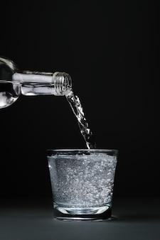 Mineralwasser wird in eine dunkle wand aus glas in nahaufnahme mit kopierraum und selektivem fokus gegossen.