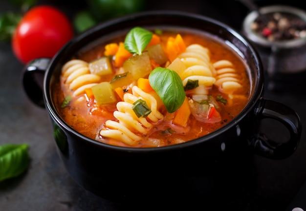 Minestrone, italienische gemüsesuppe mit teigwaren auf schwarzen hintergründen.