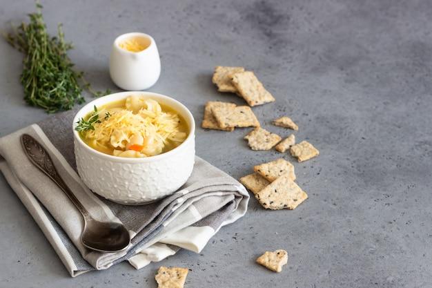 Minestrone mit nudeln und weißen bohnen mit thymian belegt und mit crackern serviert
